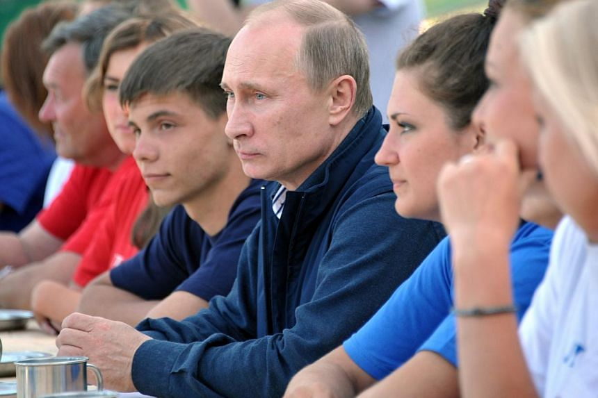 Russia's President Vladimir Putin (centre) meets with members of the Russian Geographical Society's expedition on the Gogland Island in the Gulf of Finland in the Baltic Sea on July 15, 2013. Russian President Vladimir Putin has accused the Unit