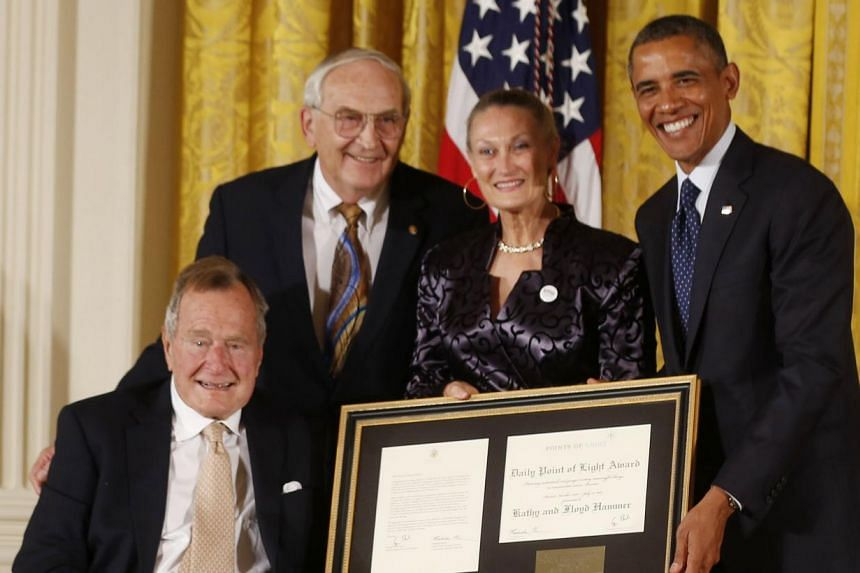 President Barack Obama, right, with former President George H. W. Bush, left, present the 5,000th Daily Point of Light Award to Mr Floyd Hammer and Ms Kathy Hamilton, centre, from Union, Iowa, in the East Room of the White House in Washington on Mond