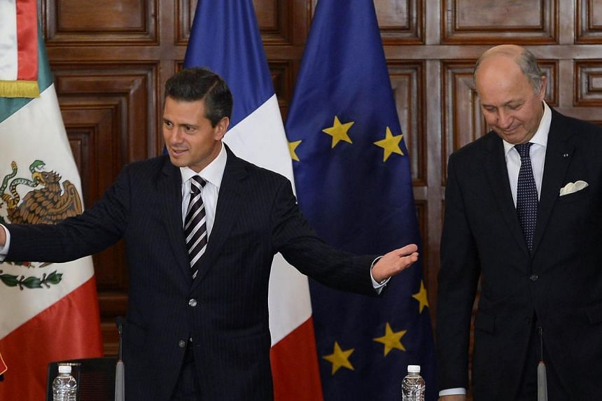 Mexico's President Enrique Pena Nieto (left) and France's Foreign Minister Laurent Fabius take their seats before offering a press conference at the National Palace in Mexico City, on July 15, 2013. Mexico's president unveiled plans Monday for U