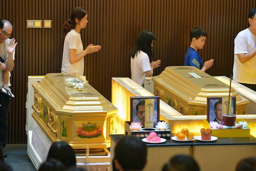 Family members walk past the coffins of the two Kovan murder victims as part of Buddhist funeral rites. -- ST PHOTO: KUA CHEE SIONG