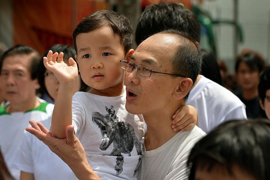 The younger son of murder victim Tan Chee Heong waves goodbye as the hearse carrying the body of his father leaves the Teochew Funeral Parlour. -- ST PHOTO: KUA CHEE SIONG
