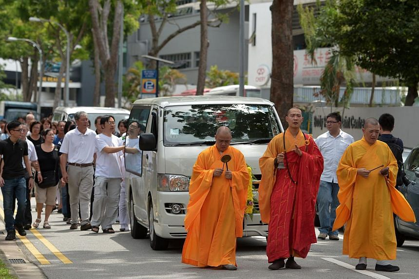 Priests lead the funeral procession of the two Kovan murder victims, Mr Tan Boon Sin, 66, and Mr Tan Chee Heong, 42. -- ST PHOTO: CAROLINE CHIA