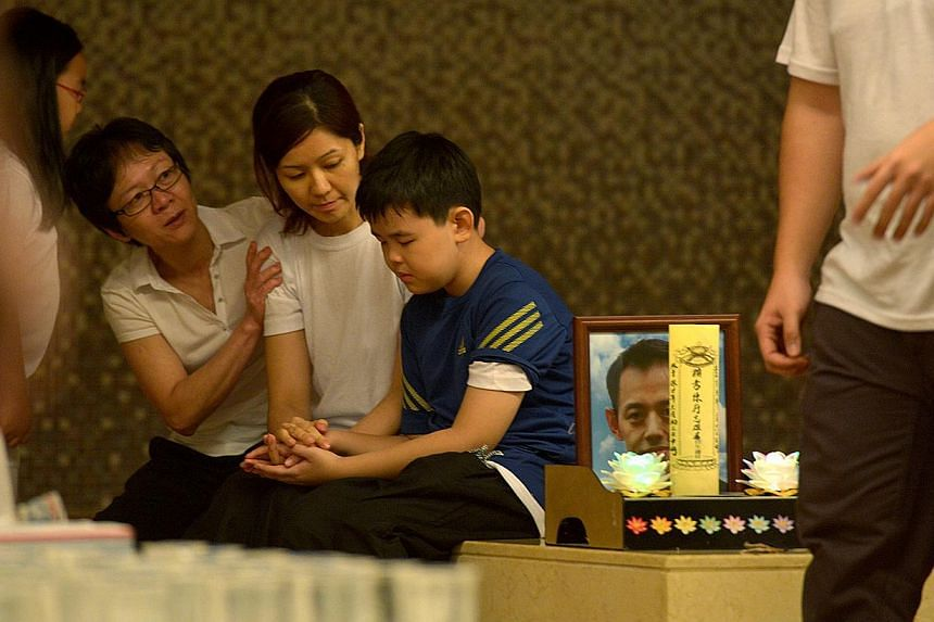 The 10-year-old son of murder victim Tan Chee Heong is comforted by his mother and other relatives after the cremation of the two Kovan murder victims at Mandai Crematorium. -- ST PHOTO: CAROLINE CHIA