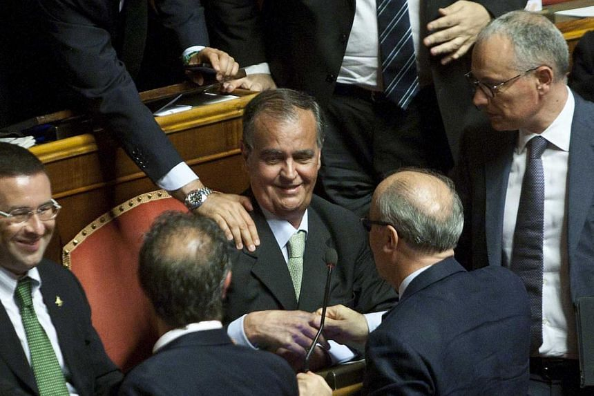 Italian Senate Vice President Roberto Calderoli (centre) is greeted inside the Senate, in Rome on Tuesday, July 16, 2013. An Italian senator who compared the country's first black minister to an orangutan said he did a silly thing and offered to send