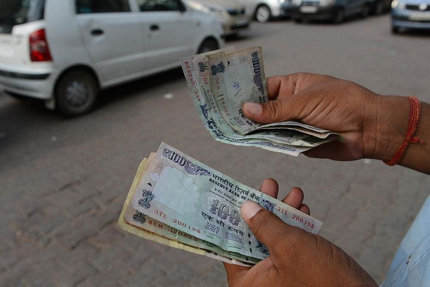 In this photograph taken on June 26, 2013, a car park attendant counts Indian rupee notes in New Delhi. The Reserve Bank of India (RBI) announced measures late on Monday to curb the rupee's decline by tightening liquidity and making it costlier for b