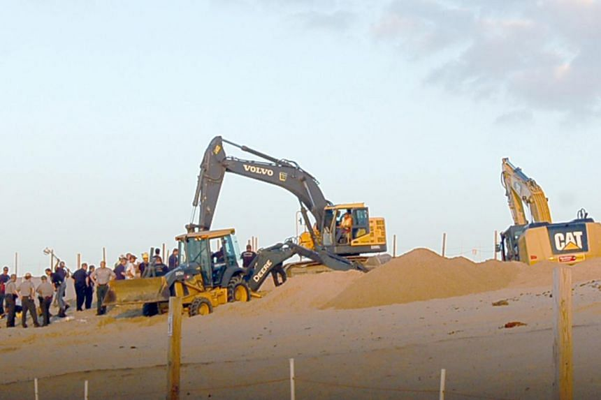 In this July 12, 2013, photo rescue workers with heavy equipment working to free 6-year-old Nathan Woessner who fell into a hole in a massive sand dune at the Indiana Dunes National Lakeshore in Michigan City, Indianapolis. Woessner remained hospital