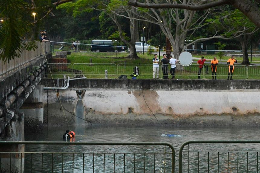 Police officers and divers looking for the murder weapon in the waters near the National Sailing Centre at East Coast Parkway on Sunday. It is not known if the weapon - believed to be a knife - was recovered. -- PHOTO: LIANHE WANBAO