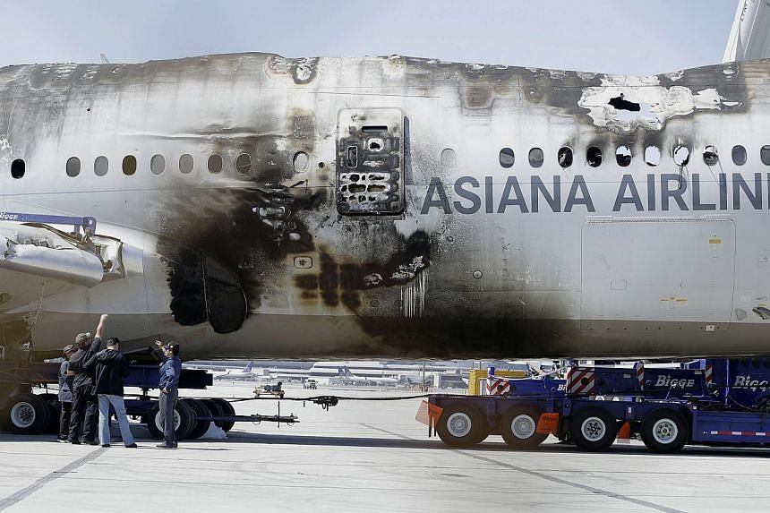A group of men look at the wreckage of Asiana Flight 214, which crashed on Saturday, July 6, 2013, at San Francisco International Airport, in San Francisco on Friday, July 12, 2013. Asiana Airlines said on Monday it will sue a TV station that incorre
