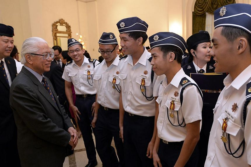 Boys' Brigade President Ho Yew Kee (left) and President Tony Tan Keng Yam (second from left) chat with award recipients Jorrick Lim (third from left), Lim Xuan Zheng, Peter Chong, Josiah Tan and Ang Zheng Shun. The five members of the Singapore Boys'
