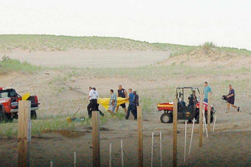 In this July 12, 2013, photo rescue workers with a stretcher carrying 6-year-old Nathan Woessner after he was pulled from a sand dune at the Indiana Dunes National Lakeshore in Michigan City, Indianapolis. Doctors said on Monday, July 15, that the bo