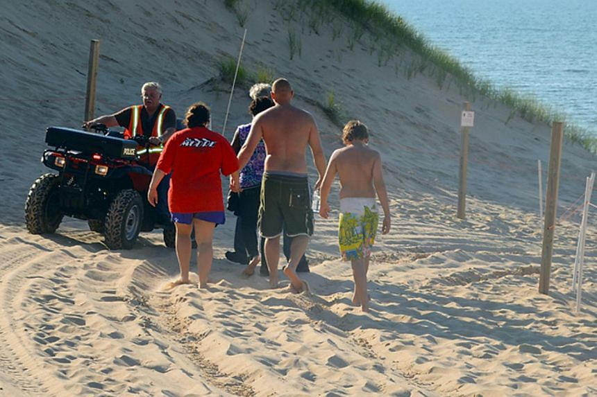 In this Friday, July 12, 2013, photo, family members of an 8-year-old boy who was buried in the sand at Mount Baldy are escorted to the beach by a Michigan City Police Department chaplain in Michigan City, Indianapolis. -- FILE PHOTO: AP