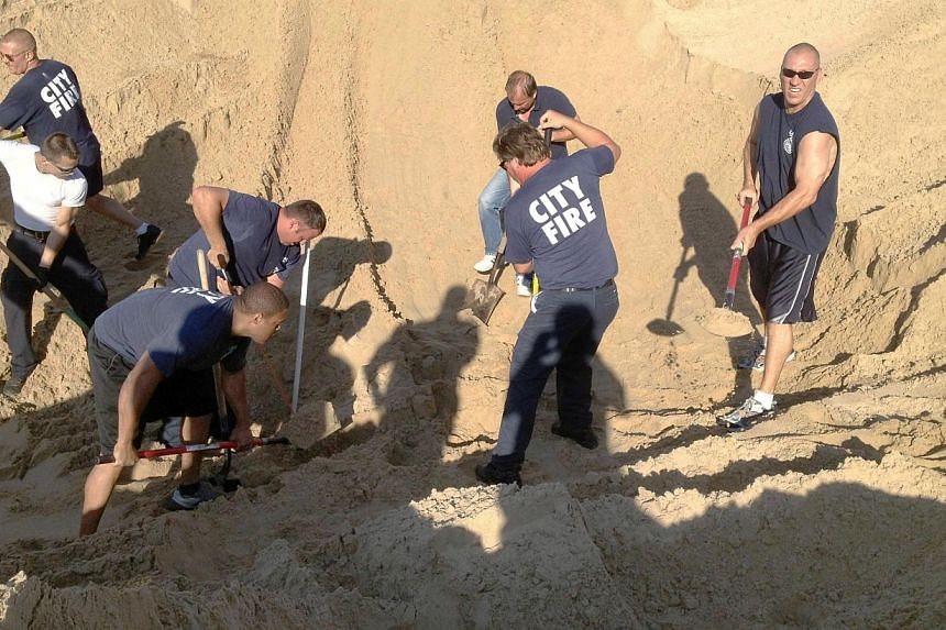 In this July 12, 2013 file photo, Michigan City police and firefighters dig with shovels to rescue Nathan Woessner, of Sterling, Illinois near Michigan City, Indianapolis. -- FILE PHOTO: AP