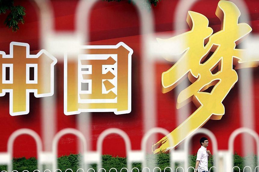"An advertisement board, seen through the fences, displays Chinese characters, which read ""China Dream"", in central Shanghai, on July 1, 2013. The characters are part of a slogan which read, ""Come together and build the China Dream"". -- PHOTO: REUTERS"