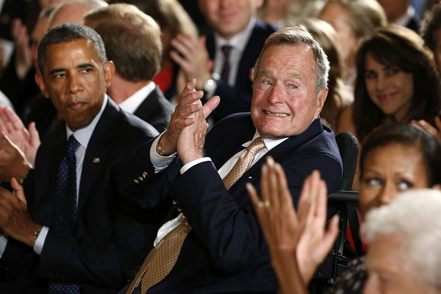 US President Barack Obama and former President George H. W. Bush applaud during an event to honour the winner of the 5,000th Daily Point of Light Award at the White House in Washington on July 15, 2013. -- PHOTO: REUTERS