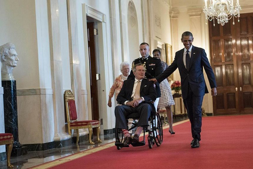 Former US First Lady Barbara Bush (left), First Lady Michelle Obama (second, right) and US President Barack Obama walk with former US president George H.W. Bush to an event in the East Room of the White House on July 15, 2013 in Washington. -- PHOTO: