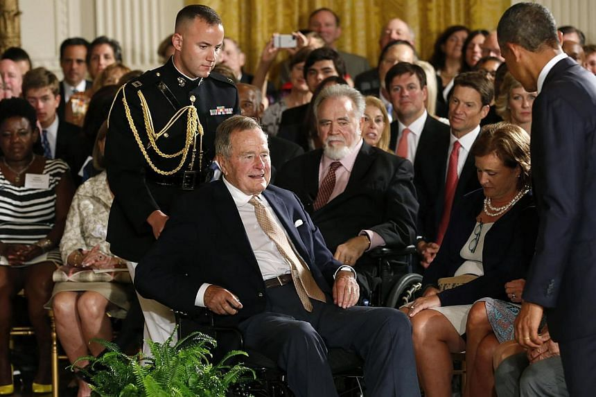 U.S. President Barack Obama (right) stands as former President George H. W. Bush is wheeled to his seat for an event to honour the winner of the 5,000th Daily Point of Light Award at the White House in Washington on July 15, 2013. -- PHOTO: REUTERS