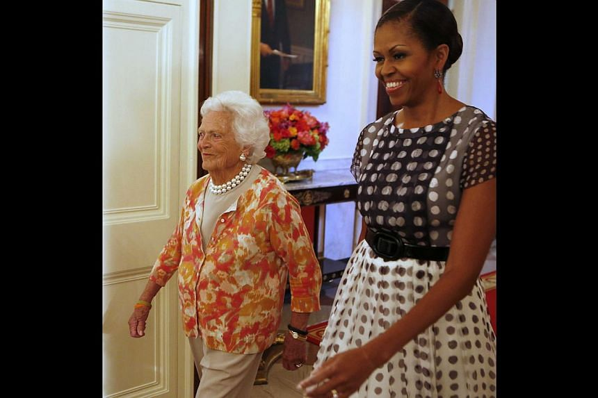 "Former first lady Barbara Bush (left) and first lady Michelle Obama walk into an event honouring the 5,000th winner of the ""Daily Point of Light"" award in the East Room of the White House in Washington on July 15, 2013. -- PHOTO: REUTERS"