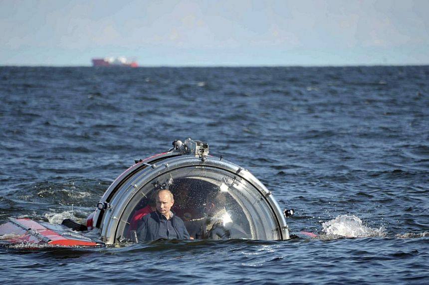 "Russia's President Vladimir Putin (left) is seen through the glass of C-Explorer 5 submersible after a dive to see the remains of the naval frigate ""Oleg"", which sank in the 19th century, in the Gulf of Finland in the Baltic Sea July 15, 2013. -- PHO"