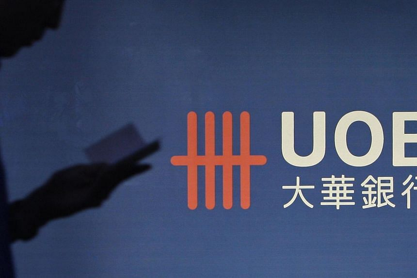 A man passes a logo of United Overseas Bank (UOB) in the Central Business District in Singapore. UOB will be issuing perpetual capital securities to raise $850 million. -- FILE PHOTO: REUTERS