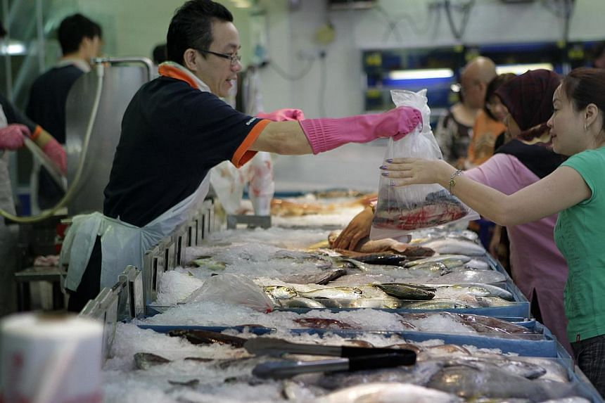Shoppers in the fresh fish section at the Sheng Siong supermarket in Bedok on Feb 25, 2011.Singapore fish importers are paying at least 20 per cent more for five types of fish banned for export for two months by Malaysia. -- ST FILE PHOTO: KEVI