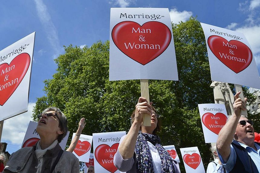 Demonstrators protesting against a gay marriage bill hold placards outside of the Houses of Parliament in London on June 3, 2013. -- FILE PHOTO: REUTERS