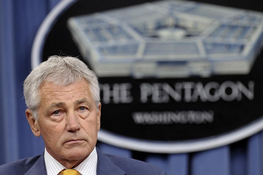 In this June 26, 2013 file photo Defence Secretary Chuck Hagel listens during a news conference at the Pentagon. Mr Hagel said on Tuesday that a new round of automatic spending cuts next year would force the department to cut personnel and that he al