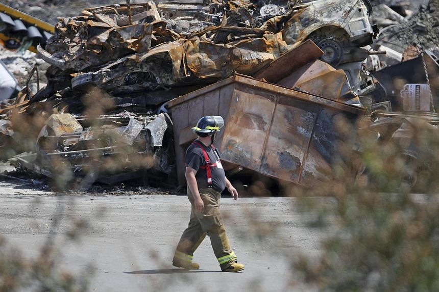 A firefighter walks past a pile of debris in Lac-Megantic on July 14, 2013.-- FILE PHOTO: REUTERS