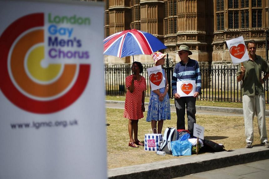 Opponents to same sex marriage hold a vigil next to the London Gay Men's Choir as they perform in front of the Houses of Parliament in central London, on July 15, 2013. -- FILE PHOTO: REUTERS