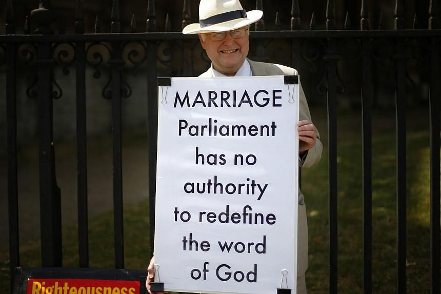 An opponent to same sex marriage holds a placard outside the Houses of Parliament in central London on July 15, 2013. -- FILE PHTOO: REUTERS