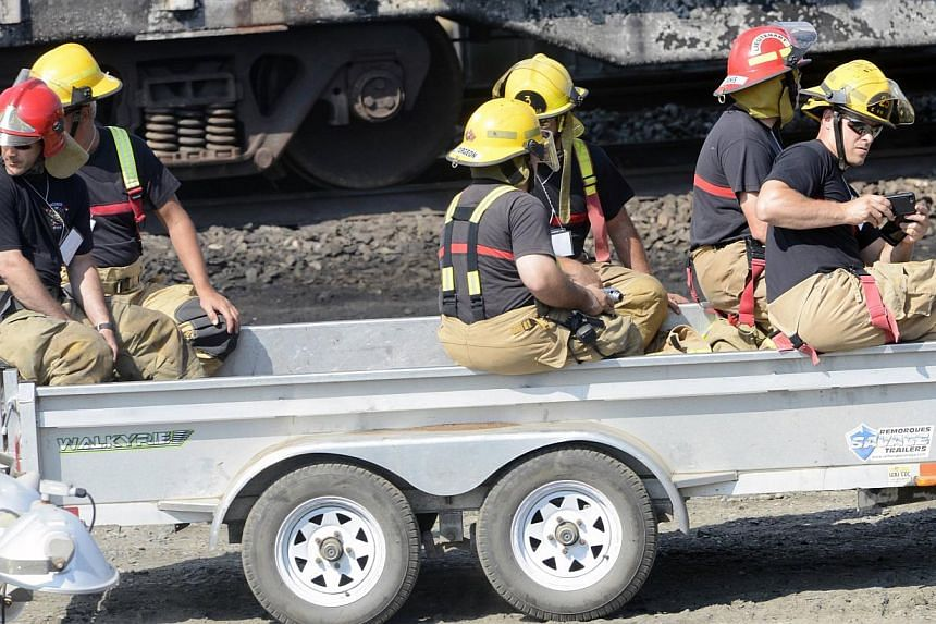 Firefighters are carried around the site of the train wreck in Lac Megantic, on July 16, 2013.-- FILE PHOTO: REUTERS