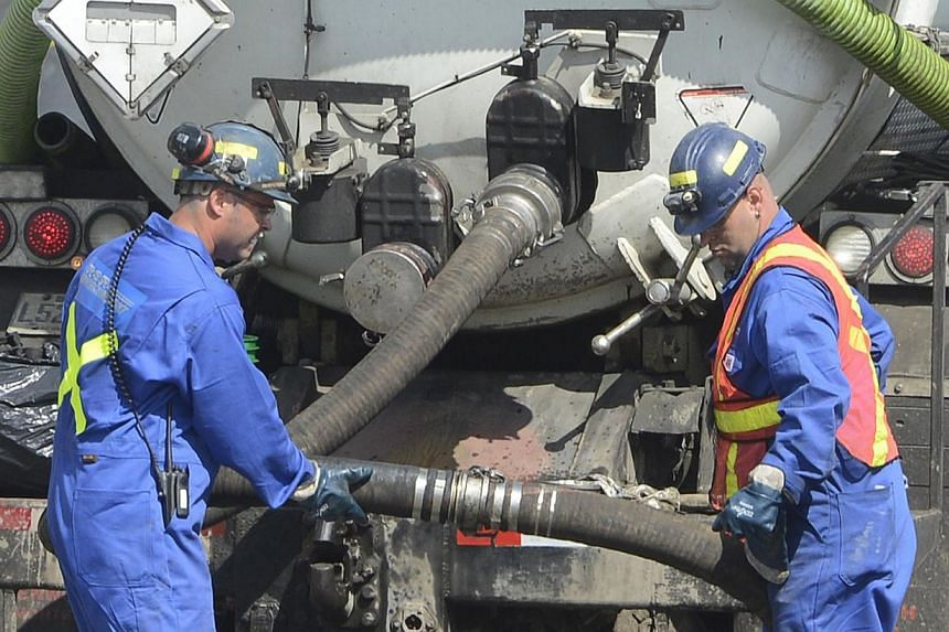 A cleaning crew work on the site of the train wreck in Lac Megantic, on July 16, 2013.-- FILE PHOTO: REUTERS