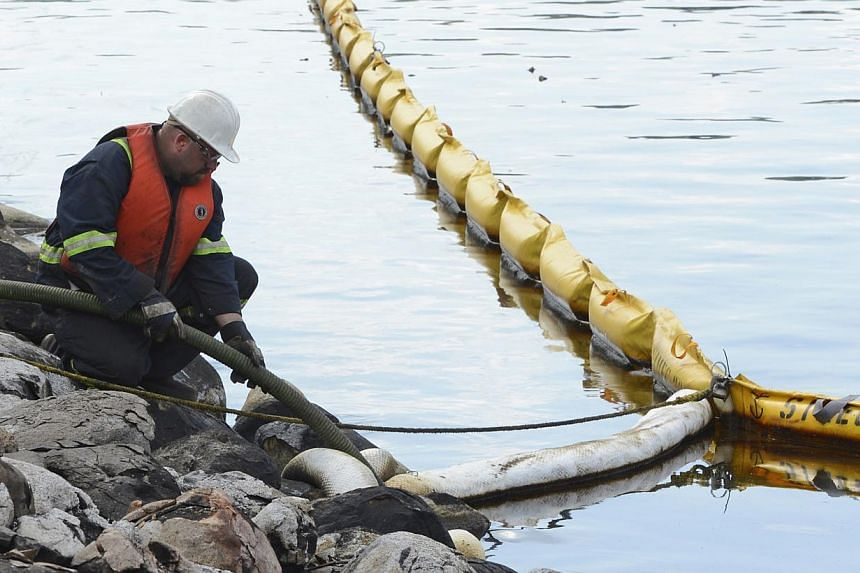 A worker pumps oil from the lake near the site of the train wreck in Lac Megantic, on July 16, 2013. -- FILE PHOTO: REUTERS