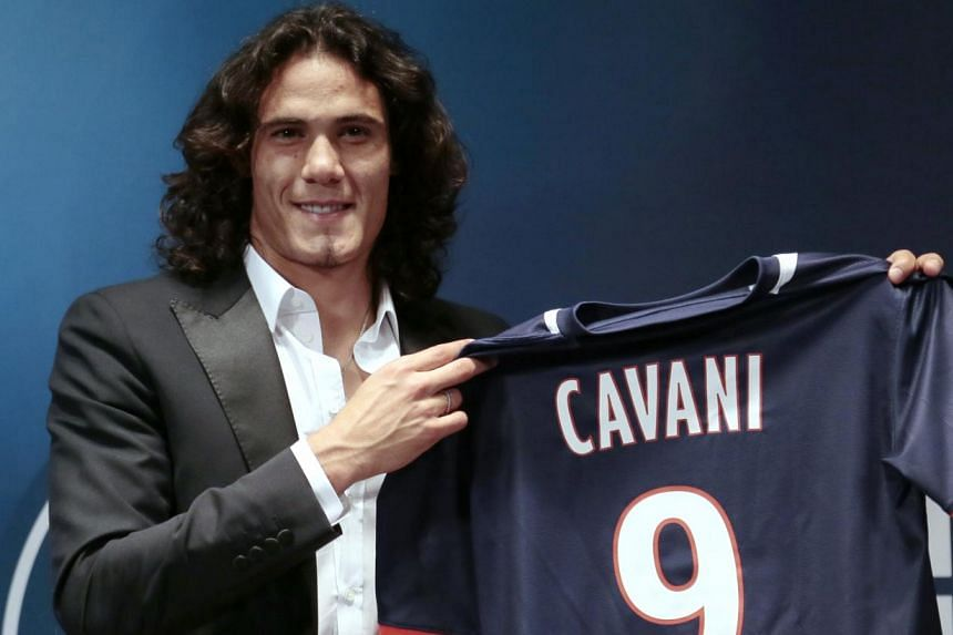 Paris Saint-Germain's (PSG) new forward, Edinson Cavani of Uruguay, poses with his jersey during a press conference in Paris on July 16, 2013 after finalising his transfer. Cavani was officially unveiled as PSG's latest mega-signing, joining the Fren