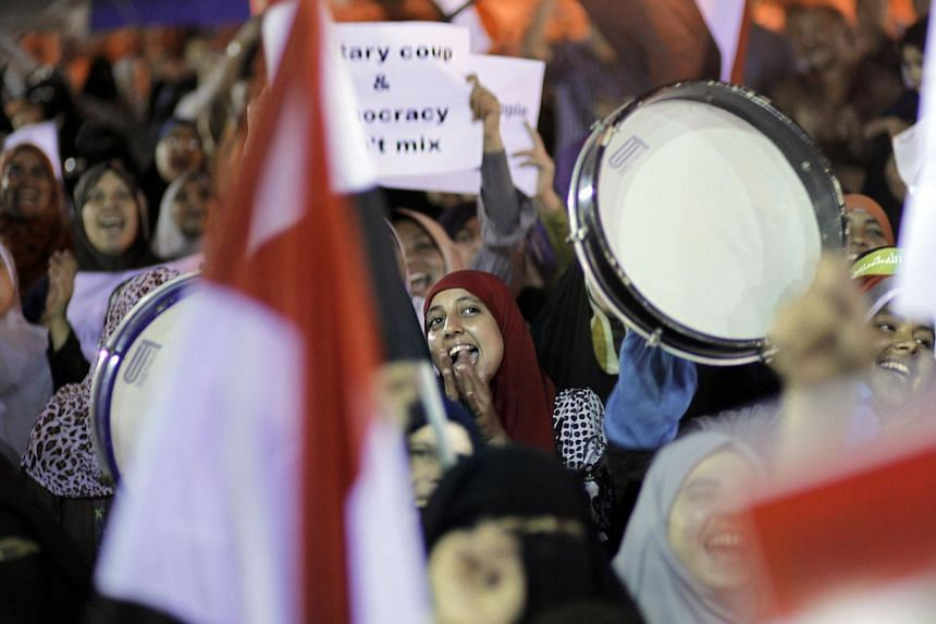 Supporters of Egypt's ousted president Mohammed Mursi chant supporting slogans during a rally in a park in front of Cairo University, where protesters have installed their camp in Giza, south-west of Cairo, Egypt on Tuesday, July 16, 2013. Egypt's ne