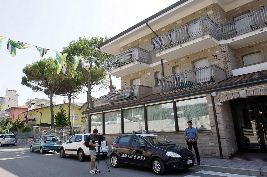 A Carabinieri police officer stands outside the hotel where Jamaican sprinters Asafa Powell and Sherone Simpson stayed in Lignano Sabbiadoro, northern Italy on Tuesday, July 16, 2013. Powell's physiotherapist on Wednesday, July 17, 2013, hit back at