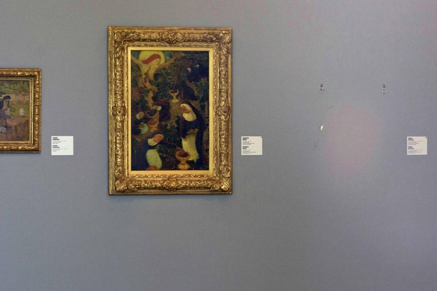 The empty space where Henri Matisse's painting La Liseuse en Blanc et Jaune was hanging (right) is seen next to a painting by Maurice Denis (centre) and Pierre Bonnard at Kunsthal museum in Rotterdam, Netherlands, on Oct 16, 2012. Seven masterpieces