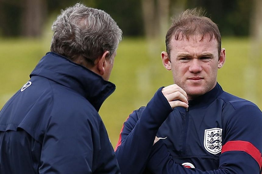 England's manager Roy Hodgson (left) speaks to Wayne Rooney during a soccer training session at the St George's Park training complex near Burton Upon Trent on Monday, May 27, 2013. Chelsea on Wednesday, July 17, 2013, said they had made a written of