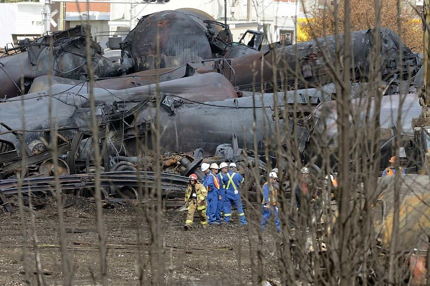 A firefighter and an emergency crew work on the site of the train wreck in Lac Megantic on July 16, 2013. Street lights melted and heavy rail lines buckled into a 5-foot arch after the explosion of a runaway train in the little Quebec town of Lac-Meg