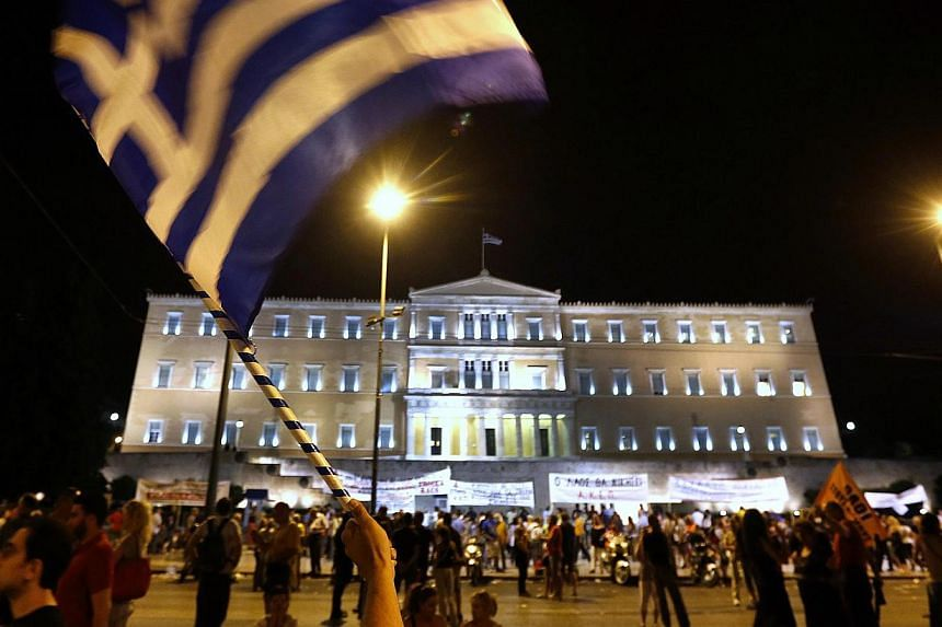 An anti-austerity protester waves a Greek flag during a rally outside the Greek parliament in central Athens on July 16, 2013. Greek lawmakers will vote on Wednesday, July 17, 2013, on a new austerity package involving a huge shake-up and maybe job c