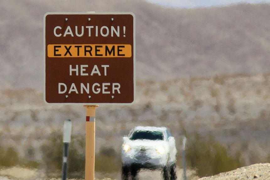 Heatwaves rise near a heat danger warning sign on the eve of the AdventurCORPS Badwater 135 ultra-marathon race on July 14, 2013, in Death Valley National Park, California. The north-eastern United States (US) sweltered on Tuesday in a scorching