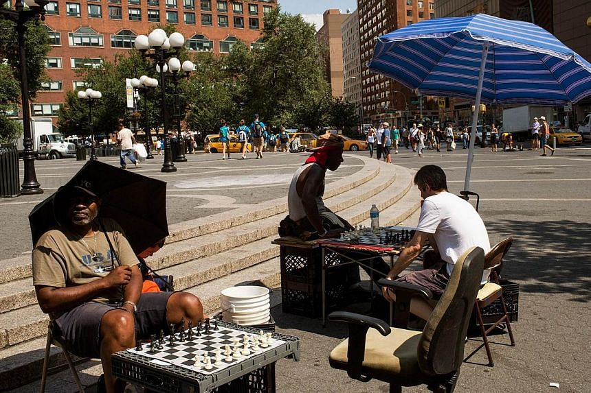 Chess players use umbrellas to find shade in Union Square on July 16, 2013, in New York City. The north-eastern United States (US) sweltered on Tuesday in a scorching summer heatwave, complete with stagnant, sticky air and no winds for relief, f