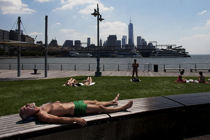 A man sunbathes in Hudson River Park during a heatwave, Tuesday, July 16, 2013, in New York. The north-eastern United States (US) sweltered on Tuesday in a scorching summer heatwave, complete with stagnant, sticky air and no winds for relief, forecas