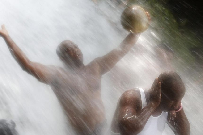 Haitians bathe in a waterfall believed to have healing powers during the annual pilgrimage to Saut d'Eau in central Haiti, July 16, 2013. Pilgrims converge on this place where according to legend, the Virgin Mary appeared atop a palm tree and where t
