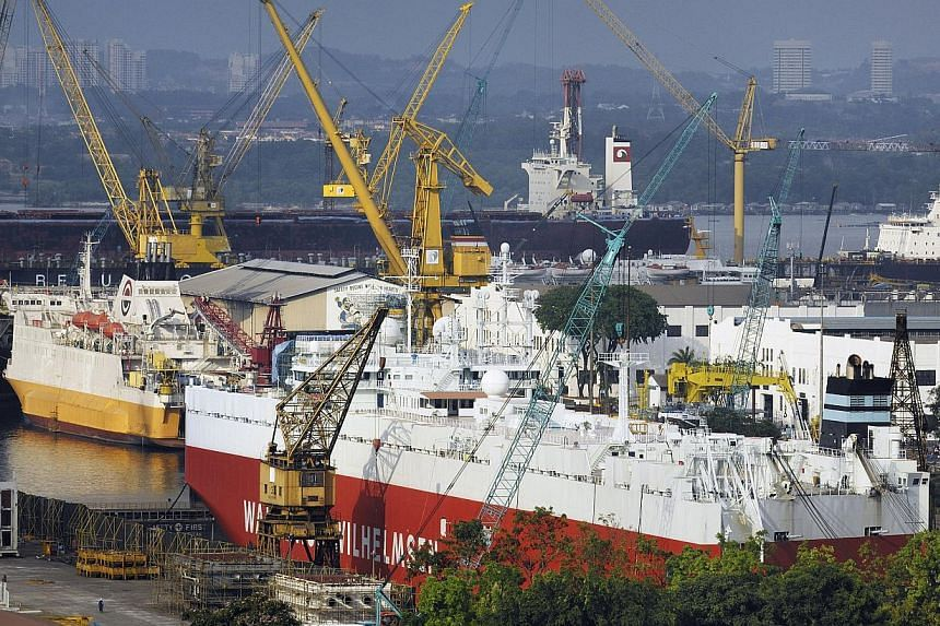 A bulk cargo ship (foreground) and other vessels undergo repairs at Sembcorp Marine Ltd's Sembawang Shipyard drydocks in Singapore, on Feb. 24, 2010. Singapore's Sembcorp Marine and Keppel Corp, the world's top offshore rig-makers, stand to be among