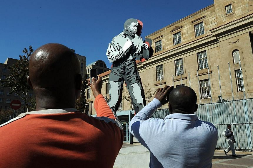"Men takes pictures of the statue of former South African President Nelson Mandela as a boxer in downtown on Johannesburg on July 17, 2013. Mr Mandela will spend his 95th birthday in hospital on Thursday, but was said to be making ""remarkable"" pr"