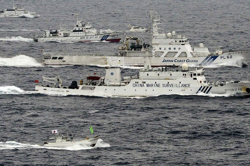 An aerial photo shows a Chinese marine surveillance ship (centre) cruising next to Japan Coast Guard patrol ships in the East China Sea, near what are known as the Senkaku isles in Japan and the Diaoyu islands in China, on April 23, 2013. On Th