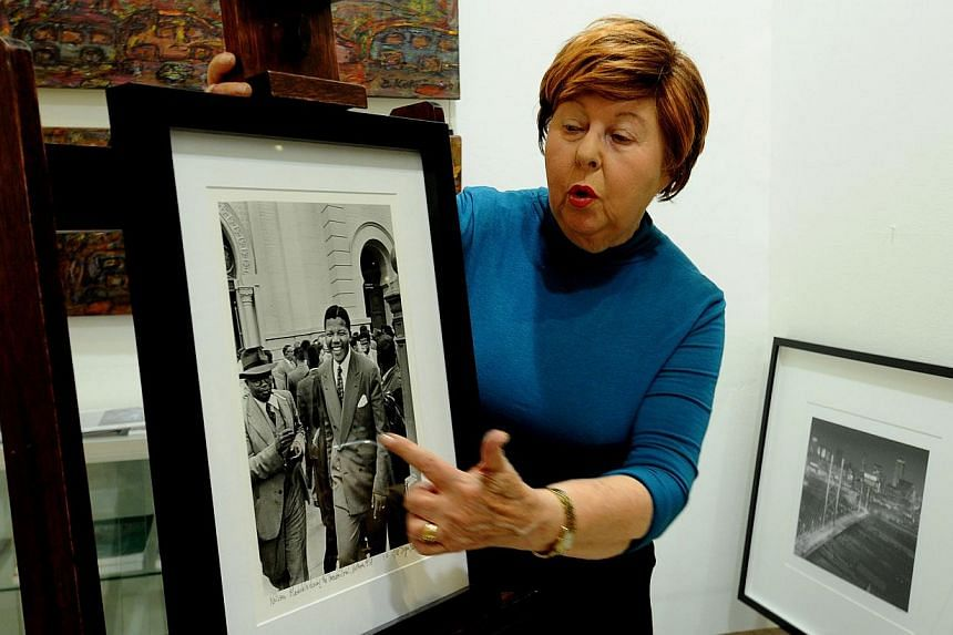 A gallery worker points at a photo of former South African President Nelson Mandela on July 17, 2013, during the hanging of artwork for an exhibition in Johannesburg, focusing on the anti-apartheid hero to mark his 95th birthday. Mr Mandela will spen
