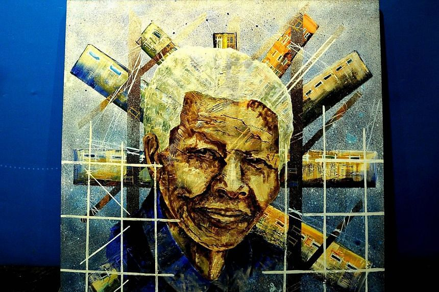 An oil painting called Mandela In Global Icon by Daniel Mosako sits on July 17, 2013, during the hanging of artwork for an exhibition in Johannesburg, focusing on the anti-apartheid hero to mark his 95th birthday. Mr Mandela will spend his 95th