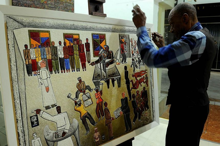 South African artist Alfred Thoba (right) fixes his painting, called Mandela And The Constitution on July 17, 2013, during the hanging of artwork for an exhibition in Johannesburg, focusing on the anti-apartheid hero to mark his 95th birthday. Mr Man