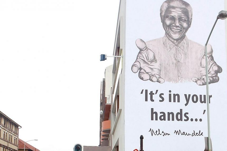 A huge banner of former President Nelson Mandela is seen as it hangs over the Hindu Tamil Instituite in Durban on July 17, 2013, in preparation to celebrate Nelson Mandela's 95th birthday and to commemorate Nelson Mandela International Day on 18 July